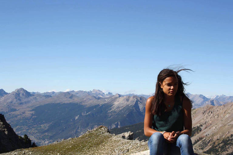 Cedella aparece sentada, olhando para o lado, com os montanhas ao fundo