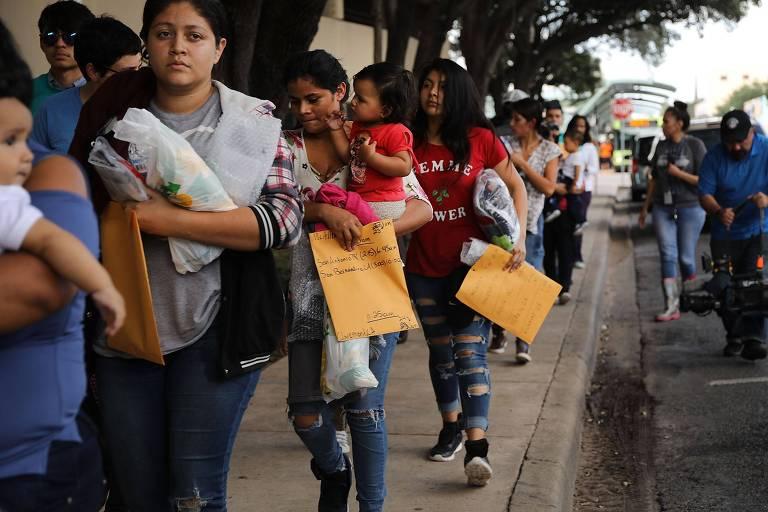 Um grupo de dez mulheres formam fila. Algumas delas carregam seus filhos no colo e envelopes de papel pardo com os documentos.