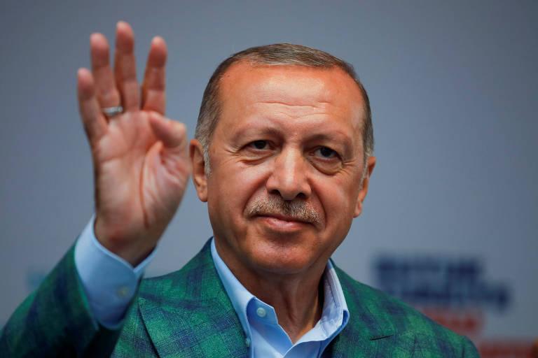Vestindo terno xadrez verde e azul e camisa azul clara, Erdogan faz o sinal do número quatro com as mãos. Ele aparece do ombro para cima.