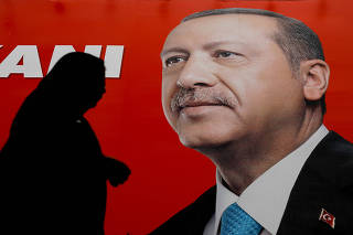 A woman passes by an election poster of Turkey's President Tayyip Erdogan in Istanbul