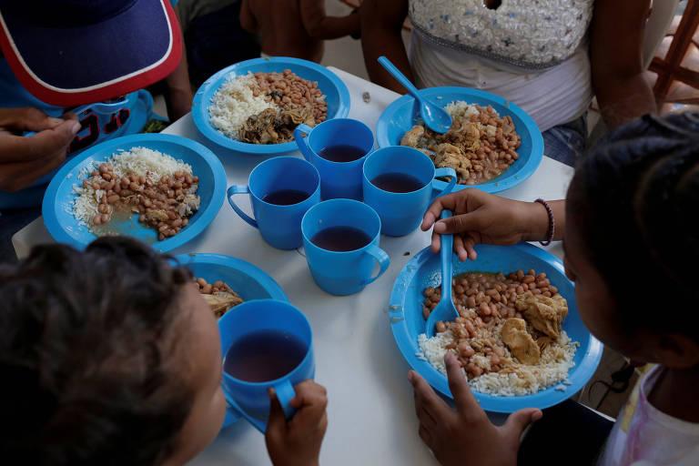 Dois adultos e duas crianças dividem uma mesa, que é vista de cima. À esquerda uma criança toma bebida de uma caneca azul, enquanto à direita um adulto come prato de arroz, feijão carioca e frango. Ao alto outras duas pessoas comem pratos com os mesmos ingredientes. No meio da mesa há quatro canecas com bebidas.