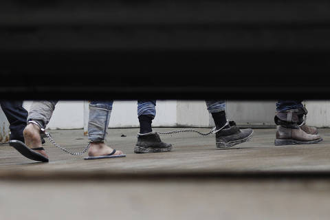 Immigrants in ankle chains disembark from a bus at the Federal Courthouse for hearings on Friday, June 22, 2018, in McAllen, Texas. (AP Photo/David J. Phillip) ORG XMIT: TXDP201