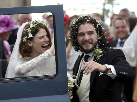 "Actors Kit Harington and Rose Leslie react as they leave after their wedding ceremony, at Rayne Church, Kirkton of Rayne in Aberdeenshire, Scotland, Saturday June 23, 2018. Former ""Game of Thrones"" co-stars Kiet Harington and Rose Leslie married near the bride's family castle in Scotland. The couple and guests arrived at Rayne Church, close to the 900-year-old Wardhill Castle in northeast Scotland, which is owned by Leslie?s family. Harington, wearing a morning suit, and Leslie, in a flowing ivory gown, smiled at members of the public who had gathered outside the church. (Jane Barlow/PA via AP) ORG XMIT: AMB831"