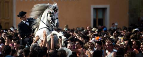 A horse rears in the crowd during the traditional San Juan (Saint John) festival in the town of Ciutadella, on the Balearic Island of Menorca, on the eve of Saint John's day on June 23, 2018.  During the island's San Juan festival, held each year on June 23 and 24, Minorcan race horses gallop and prance on their hind legs through the streets of Ciutadella to honor of the town's patron saint. As the