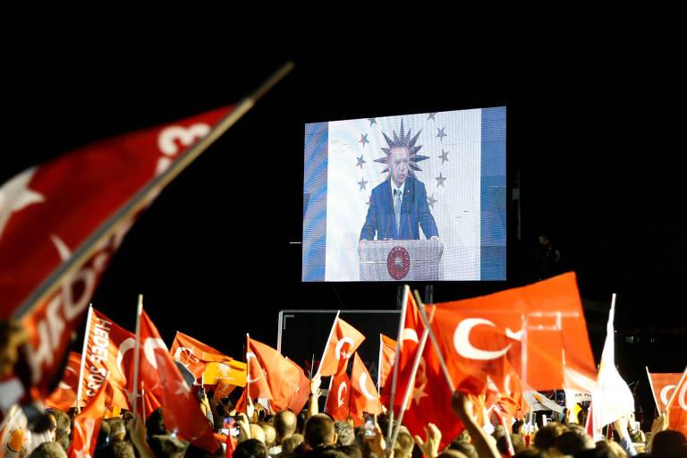 Tela exibe Tayyip Erdogan no meio bandeiras da Turquia
