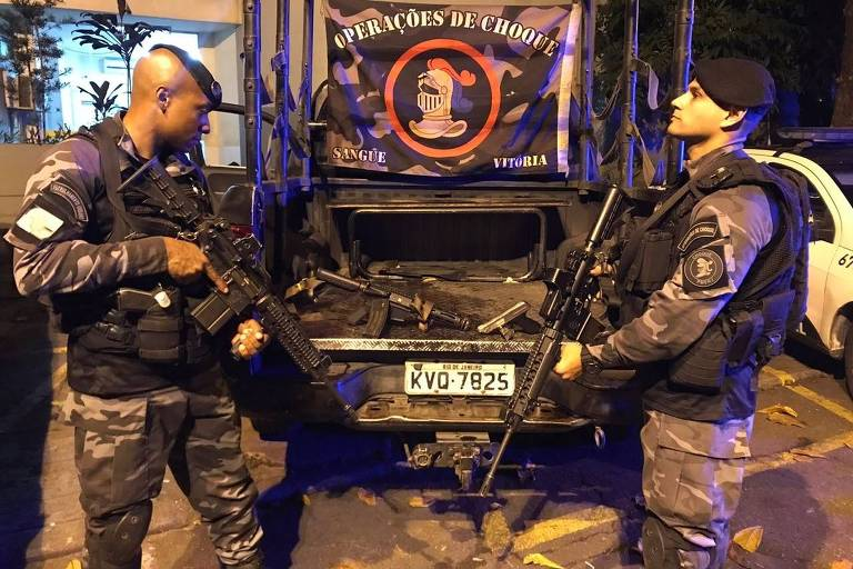 Policiais do Batalhão de Choque mostram pistola e fuzil apreendidos em operação no Rio