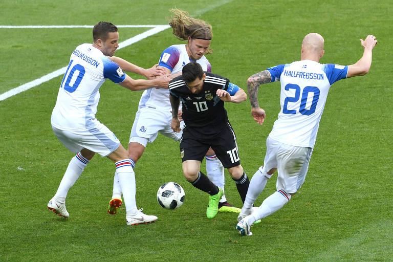 Messi tenta se desvincilhar de três marcadores islandeses na primeira rodada da Copa