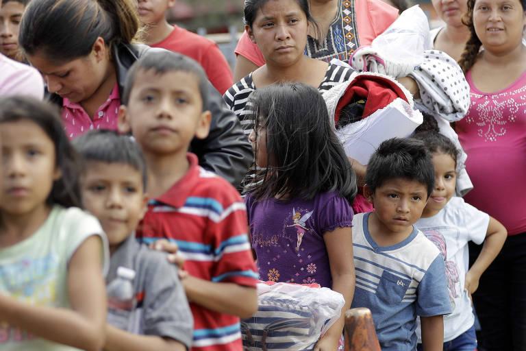 Sete crianças, sendo três meninos e quatro meninas, fazem fila ao lado de três mulheres.