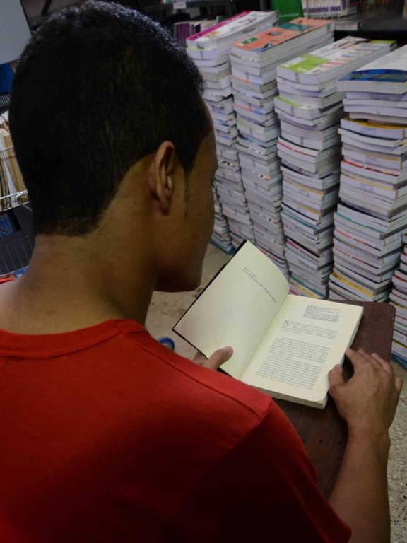 De costas, homem com uniforme de presidiário lê livro