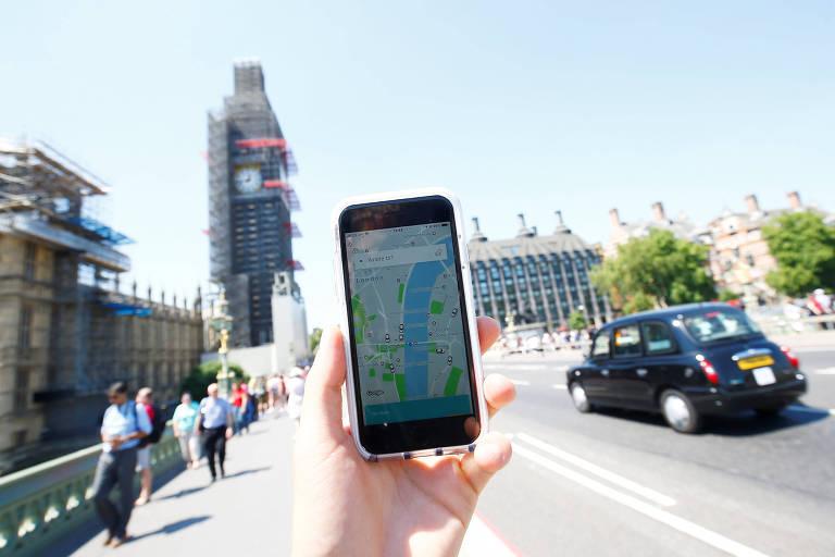 Pessoa carrega celular com aplicativo da Uber aberto no meio de uma avenida