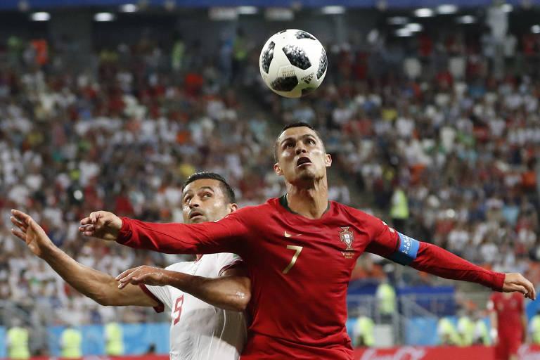 Cristiano Ronaldo e Omid Ebrahimi, do Irã, disputam a bola