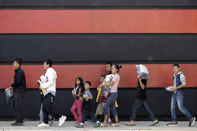 Fila com seis adultos e três crianças vistos à distância ao lado de um muro pintado com grandes faixas horizontais vermelhas e pretas