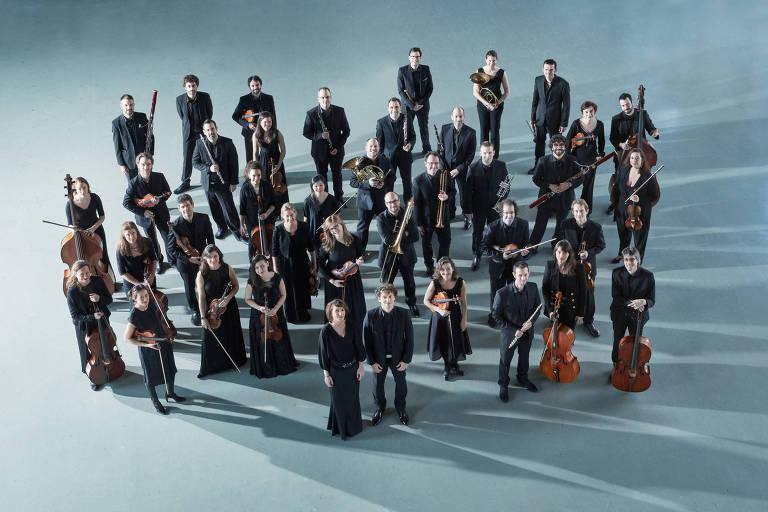 Músicos da orquestra, todos vestidos com roupas pretas, posam para foto segurando seus instrumentos