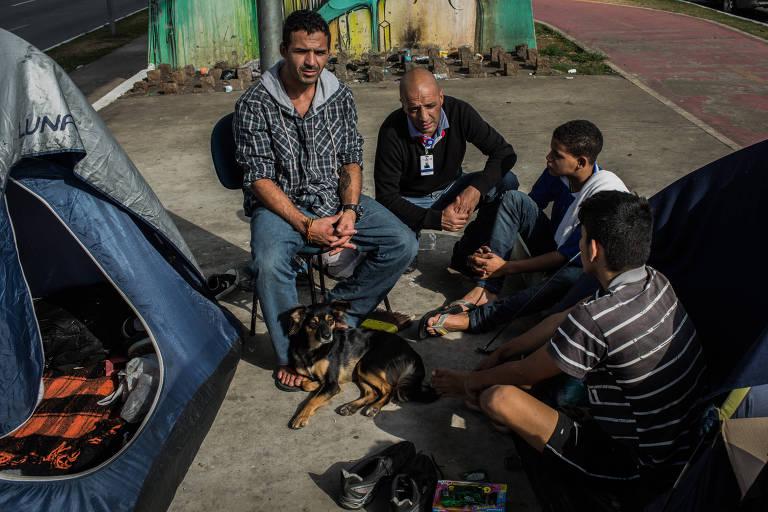 O assistente social e ex-morador de rua Adriano Diniz, 45, de crachá, conversa com moradores de rua
