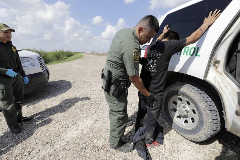 De calça jeans preta e camiseta preta, imigrante encosta com as mãos levantadas em carro da Patrulha de Fronteira, enquanto agente de farda verde o revista. Ação é observada por outro agente, que aparece na lateral esquerda em ume estrada de terra.