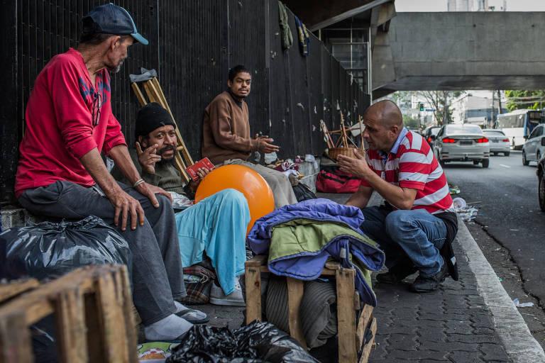Adriano Diniz (de camisa listrada em vermelho) conversa com moradores de rua
