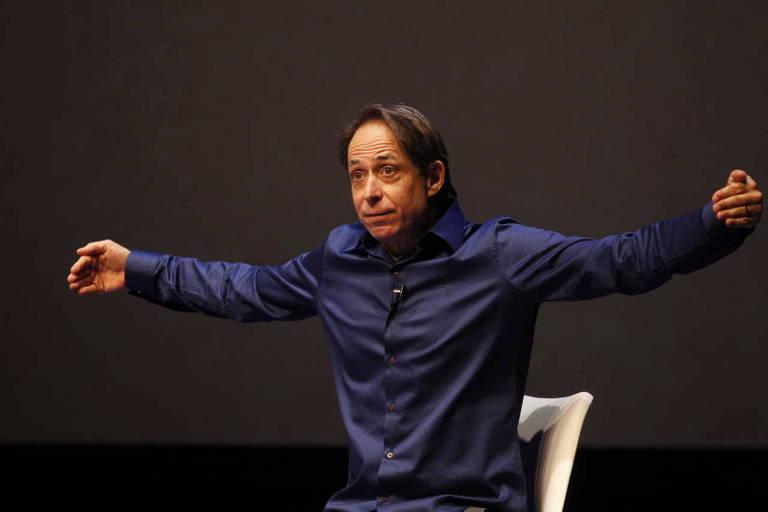 O ator Pedro Cardoso está no palco, sentado em uma cadeira de braços abertos