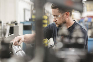 Mike Steffel, an apprentice toolmaker, works on a lathe at APT Manufacturing Solutions in Hicksville, Ohio.