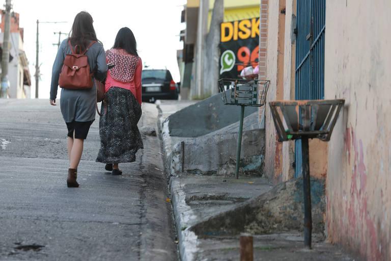 Pessoas sobem via na zona leste pela rua, devido à calçada inadequada