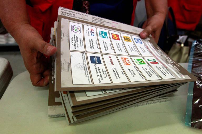 Homem movimenta cédulas de papel, que contém uma tabela de duas colunas com o nome e o logo de cada partido em cada célula