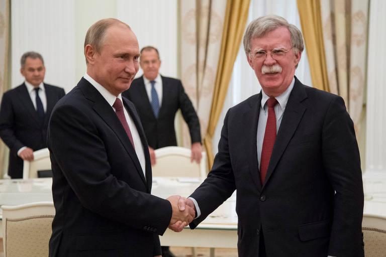 O presidente russo, Vladimir Putin (à esq.), cumprimenta o assessor americano John Bolton, em Moscou