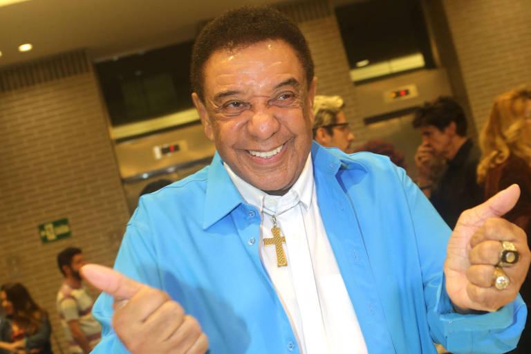 Cantor Agnaldo Timóteo de camisa azul sorri para foto