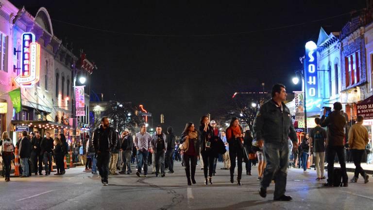 Pessoas caminhando em rua, à noite