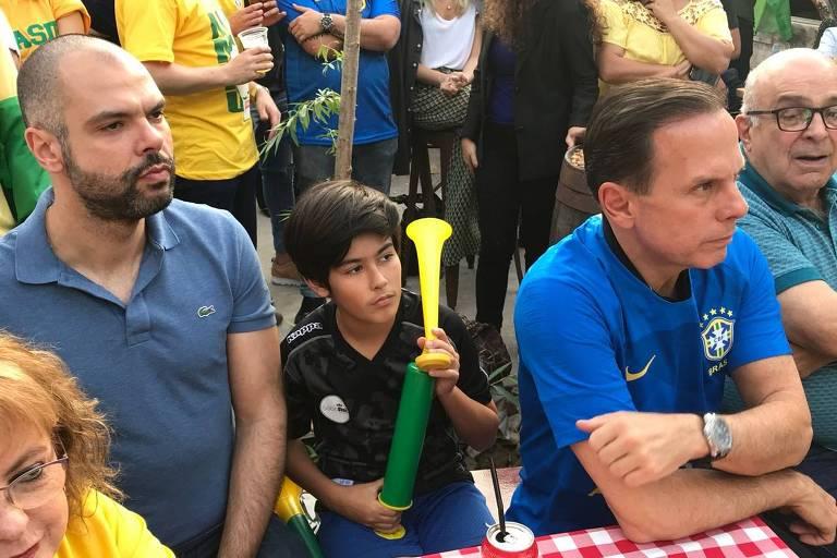 O prefeito Bruno Covas, o filho, Tomás, e o pré-candidato a governador João Doria veem o jogo do Brasil em um bar na Mooca