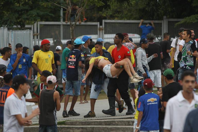 Mulher é carregada após confusão no Mineirão durante o jogo Brasil x Sérvia