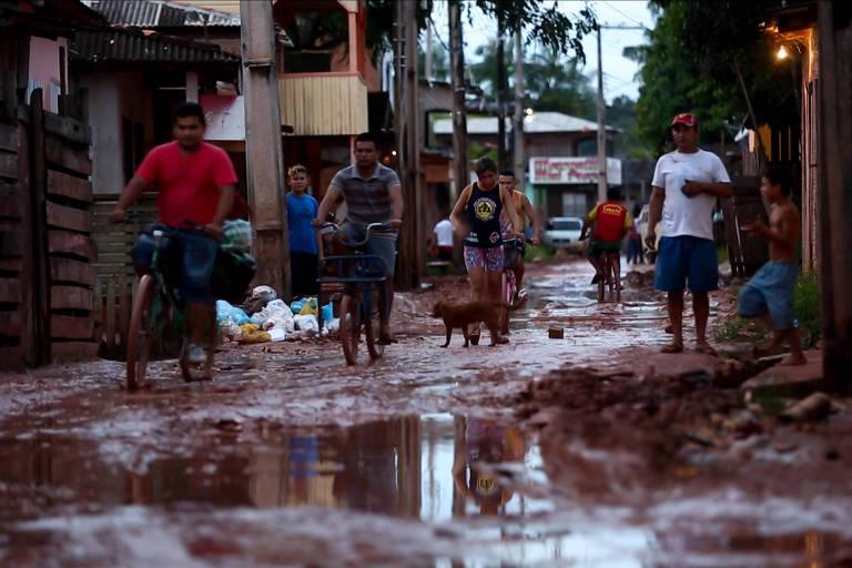 Moradores passam por rua de terra coberta de lama em Macapá