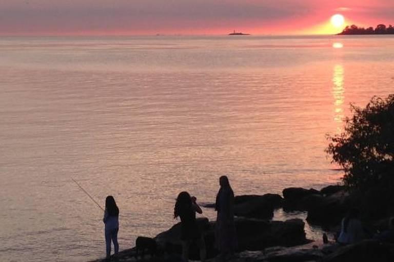 Pessoas pescando na beira de um rio