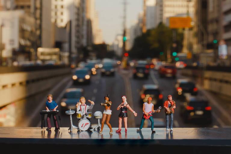 Seis bonequinhos em miniatura com mini instrumentos; ao fundo está a avenida Paulista