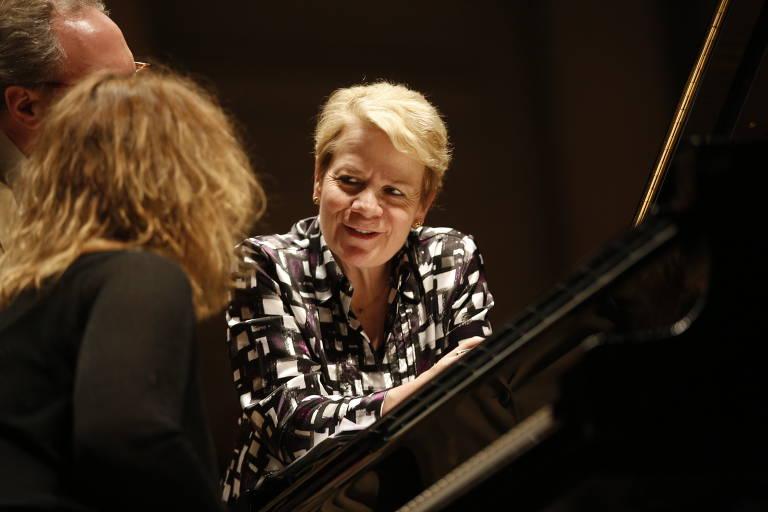 mulher conversando com outra em frente a um piano