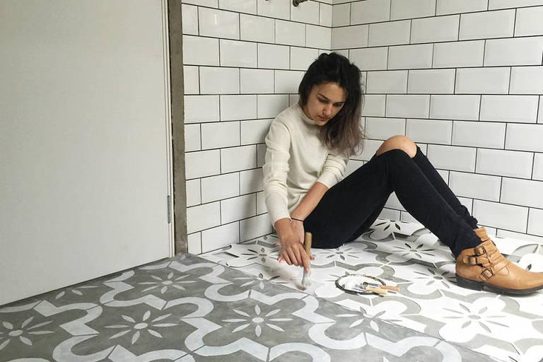 mulher fazendo estêncil no chão de concreto
