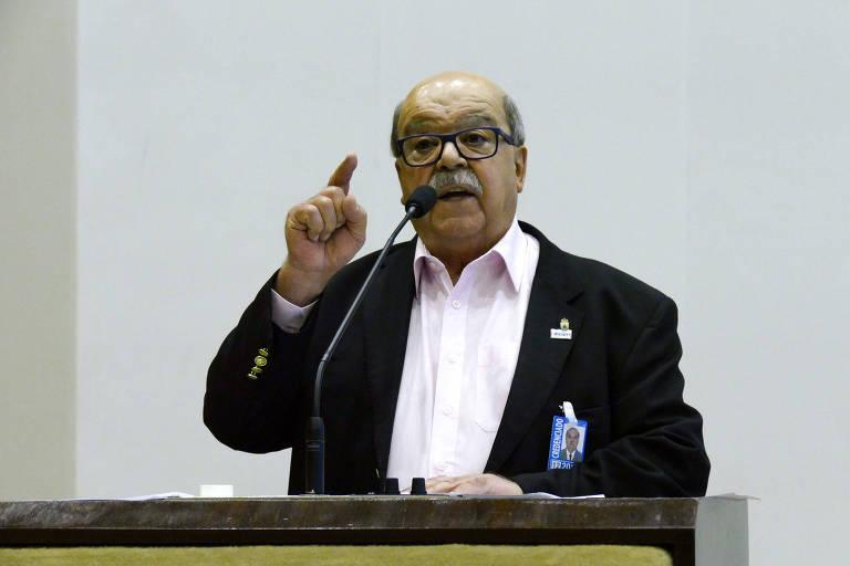 José da Fonseca fala em microfone. Ele usa óculos, caminha branca e terno preto, com um broche na lapela
