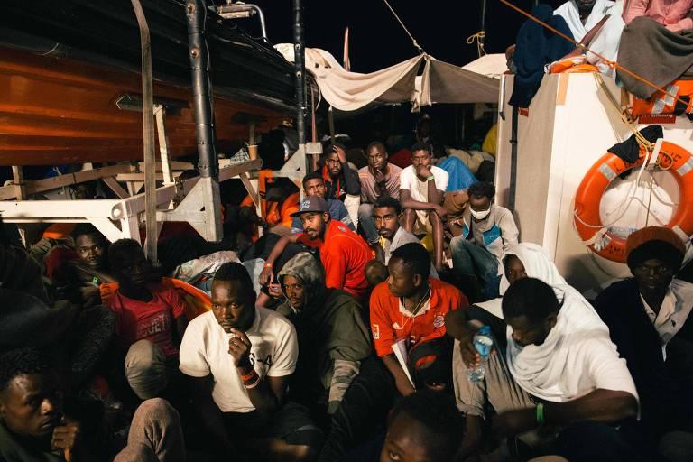Cerca de 30 homens se apertam entre a casa de máquinas e botes salva-vidas do navio Lifeline