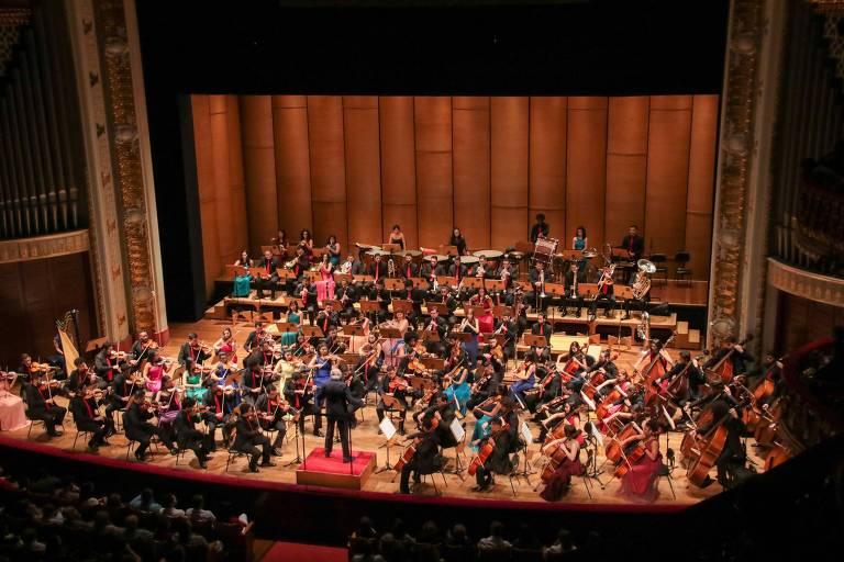 Os músicos da orquestra apresentam no palco