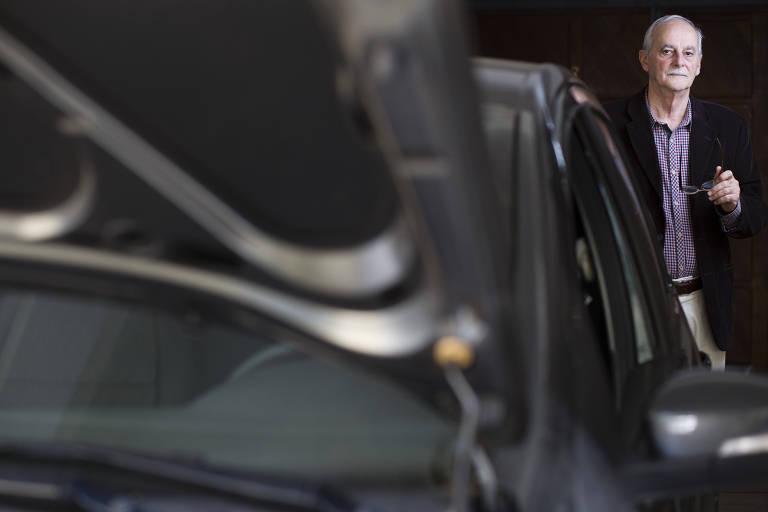 Carlos Azzolini, perito em fraude contra seguros, posa em pé atrás de um carro preto, segurando seus óculos