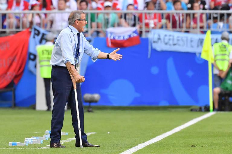 Oscar Tabarez, técnico da seleção do Uruguai, comanda equipe à beira do campo apoiado em sua muleta