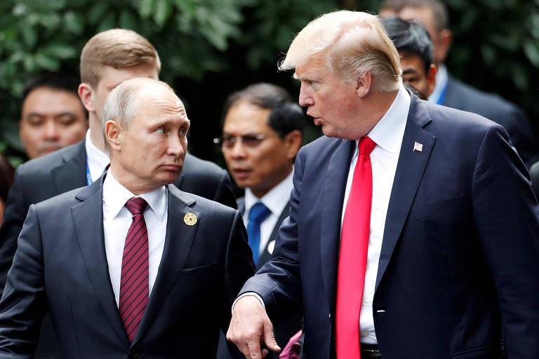 De terno preto com paletó desabotoado, camisa branca e gravata vermelha, Trump aponta para baixo enquanto conversa com Putin, que está à sua esquerda e usa terno preto com paletó abotoado, camisa branca e gravata vinho. Ao fundo, outros líderes conversam.