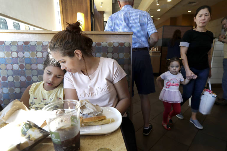 Lídia está sentada em um banco com encosto enquanto o filho, sentado à esquerda, se apoia nela. Na mesa, pratos com restos de pão e um copo de refrigerante. No corredor à direita, passa uma mulher segurando a filha.