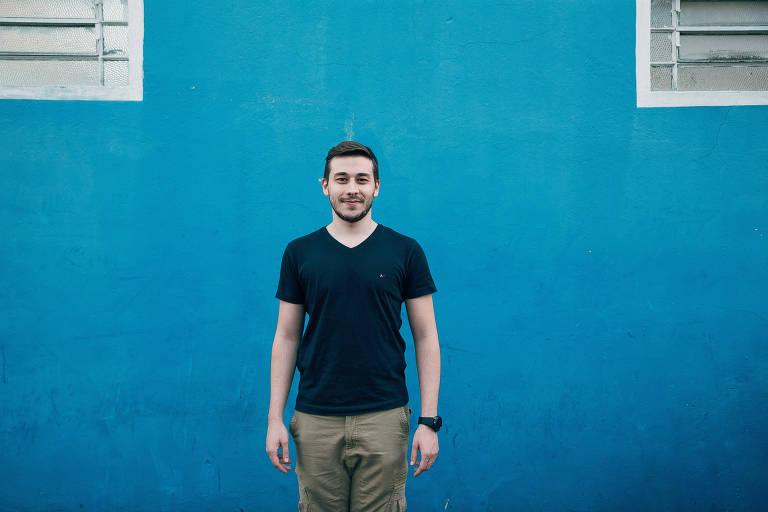 O estudante Enzo Silveira posa para foto em frente a uma parede azul