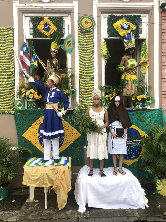 Desfile de 2 de Julho no Pelourinho, em Salvador; na foto, pessoas estão fantasiadas de índios, militares e escravos, em uma decoração verde e amarela