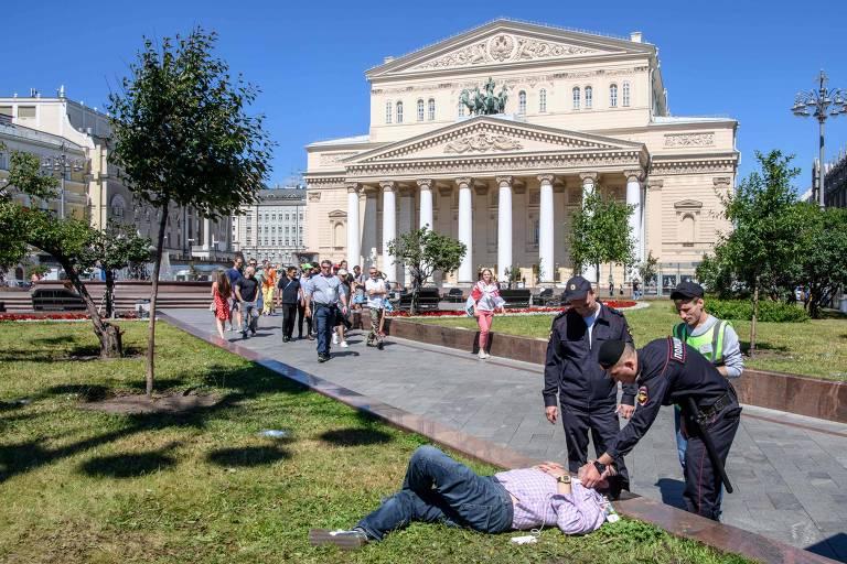 Policiais russos conferem identificação de torcedor em frente ao Teatro Bolshoi, em Moscou