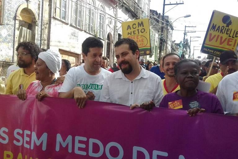 Guilherme Boulos segura faixa em meio a multidão durante desfile cívico do 2 de Julho, em Salvador