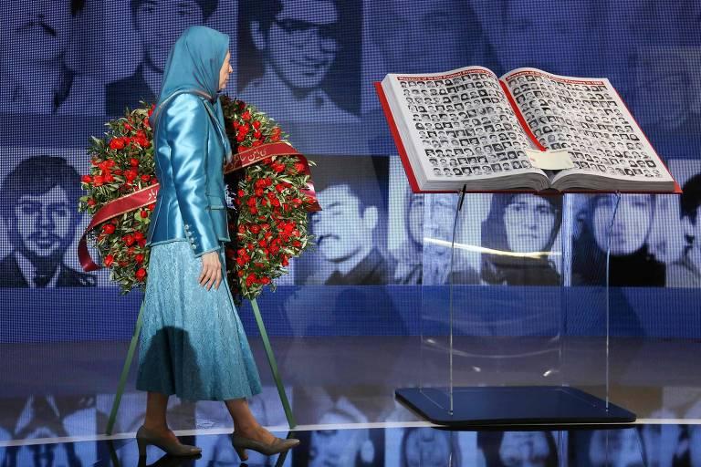 Mulher de véu e roupa longa azul caminha segurando uma coroa de flores diante de um exemplar do Corão em um paço iluminado