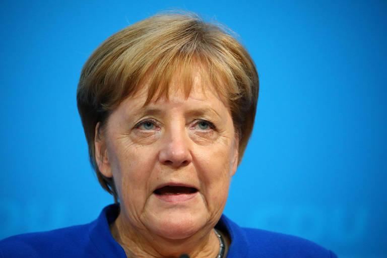 Merkel aparece com a boca aberta como se estivesse falando, do peito para cima. Ela está em um local com fundo azul, com a marca d'água de seu partido, a CDU.