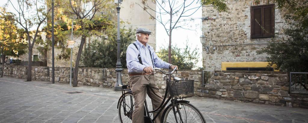 Homem de 88 anos anda de bicicleta em Acciaroli, na Itália. O índice de mortalidade caiu entre os mais velhos entre os velhos, diz um estudo italiano