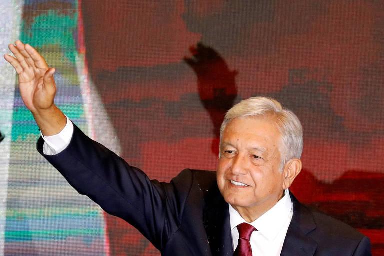 De terno preto, camisa branca e gravata vinho, López Obrador acena com a mão esquerda. Ao fundo, o pedaço da imagem de um telão.