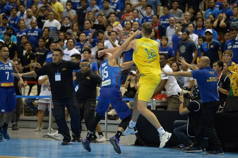 Mathew Wright (de azul), das Filipinas, e Daniel Kickert, da Austrália, trocam socos durante partida de basquete